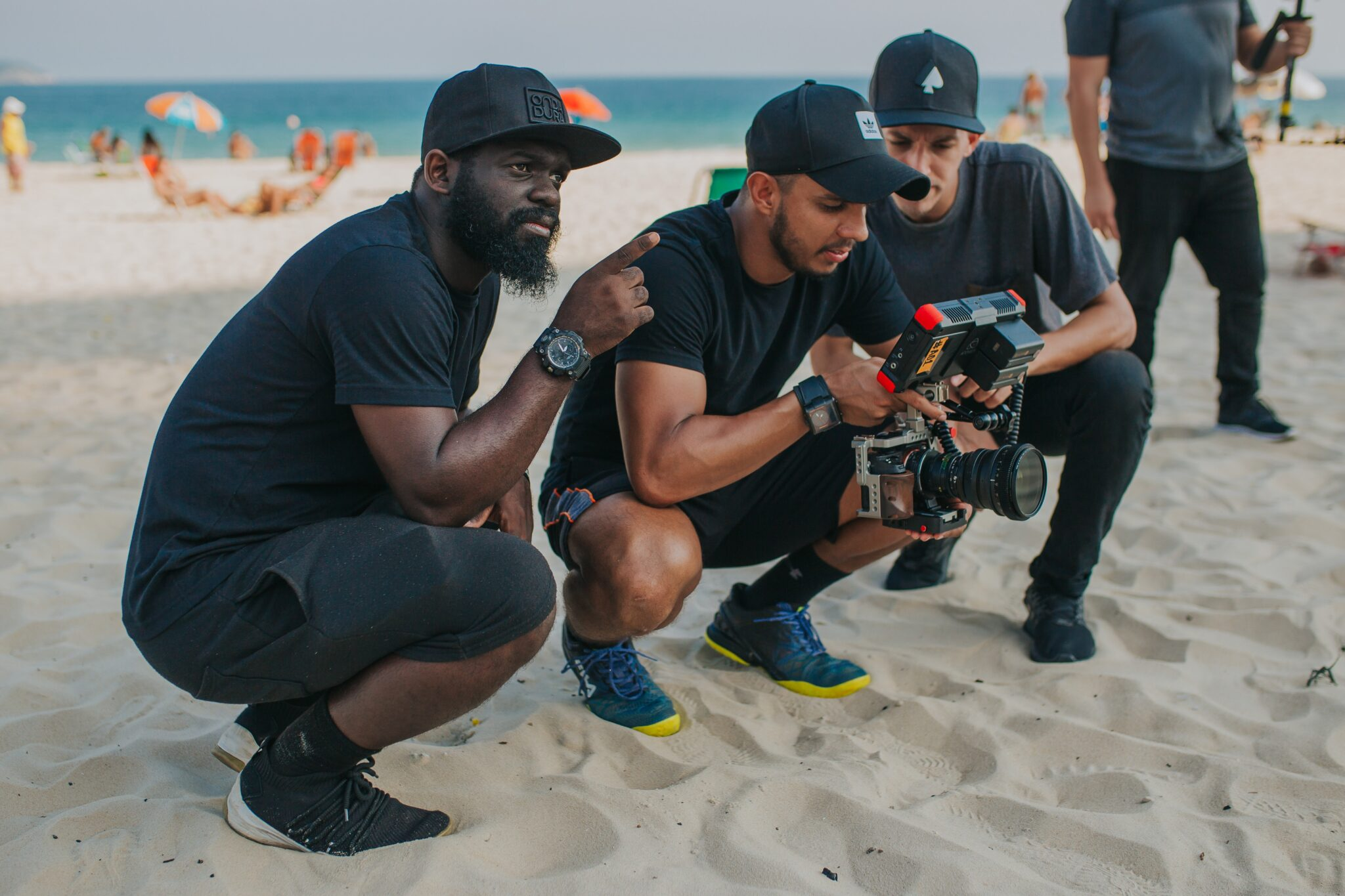 photo of of three men on a beach as part of a production crew for film or TV